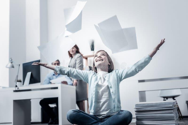 Menina entusiasmado que tem o divertimento e que joga papéis no escritório fotos de stock