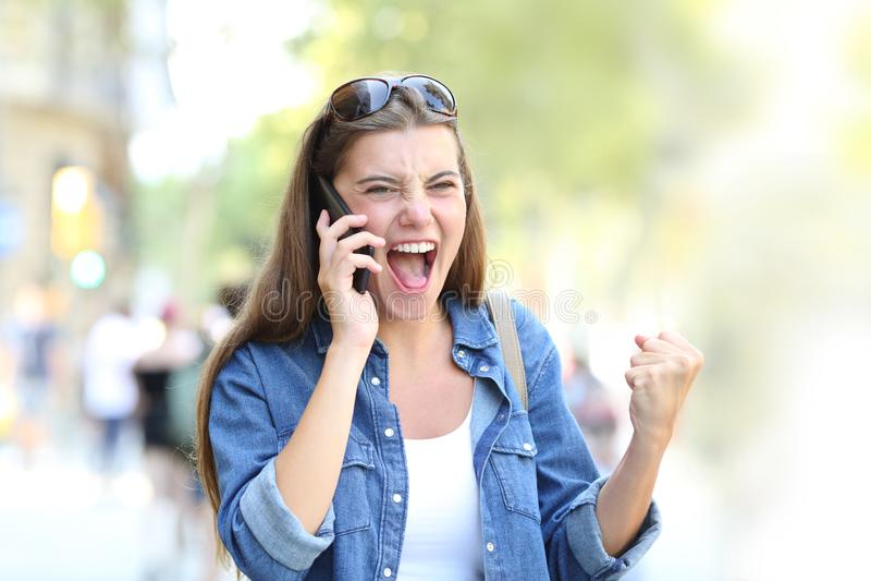 Menina entusiasmado que tem uma conversa telefônica na rua fotos de stock