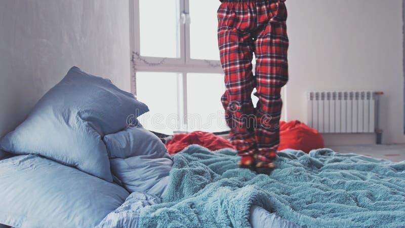 A menina entusiasmado salta na cama Feche acima dos pés fotografia de stock royalty free
