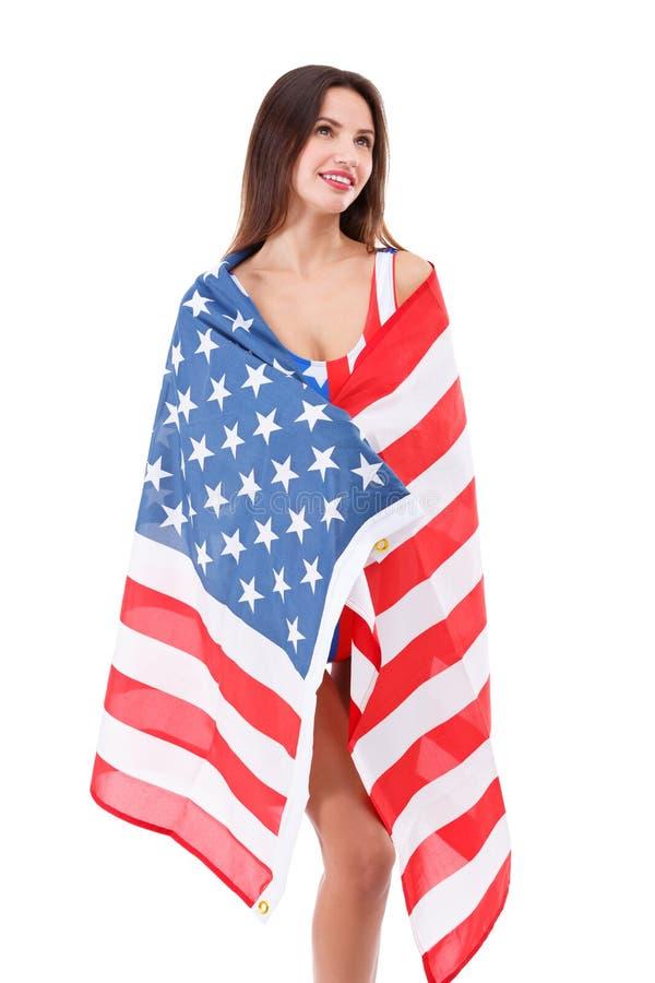 A menina envolvida acima em uma bandeira americana e na vista para cima em um branco isolou o fundo fotos de stock