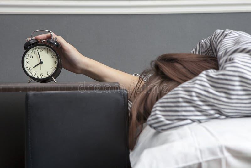 A menina, envolvida em uma cobertura listrada, põe para fora sua mão para desligar o alarme Há oito horas no despertador fotos de stock royalty free