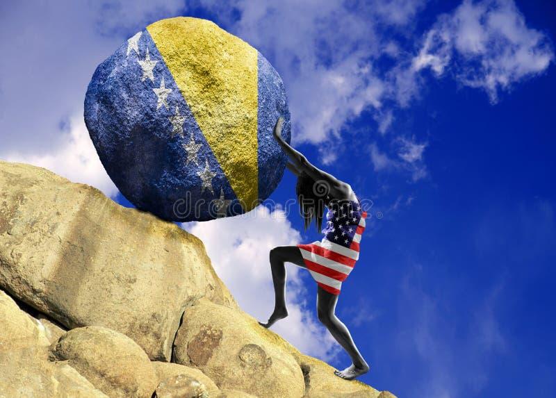 A menina, envolvida na bandeira do Estados Unidos da América, aumenta uma pedra para a parte superior sob a forma de uma silhueta imagens de stock