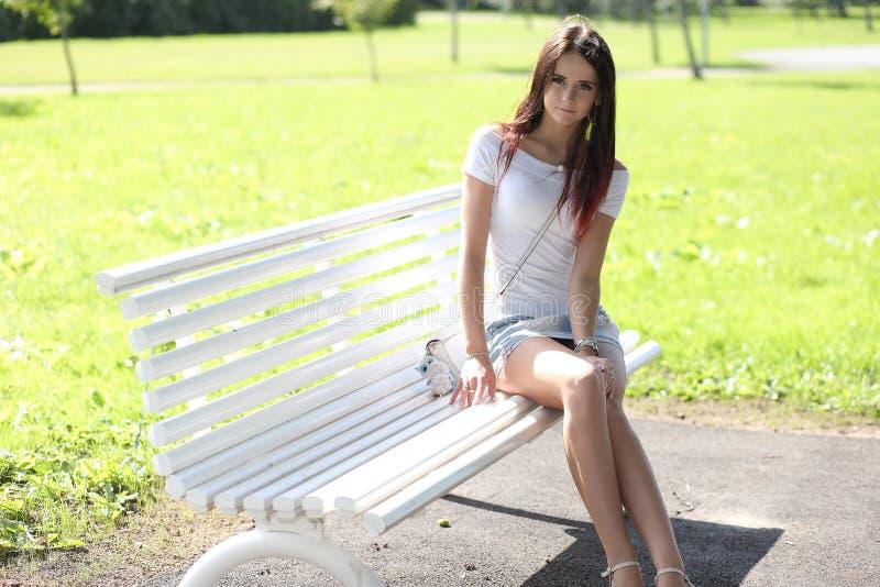 Menina erótica com a mini saia na grama verde fotos de stock
