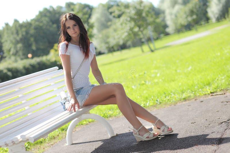 Menina erótica com a mini saia na grama verde fotografia de stock