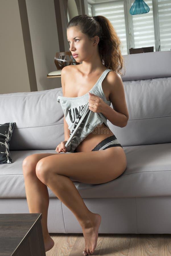 Menina erótica que senta-se no sofá imagem de stock