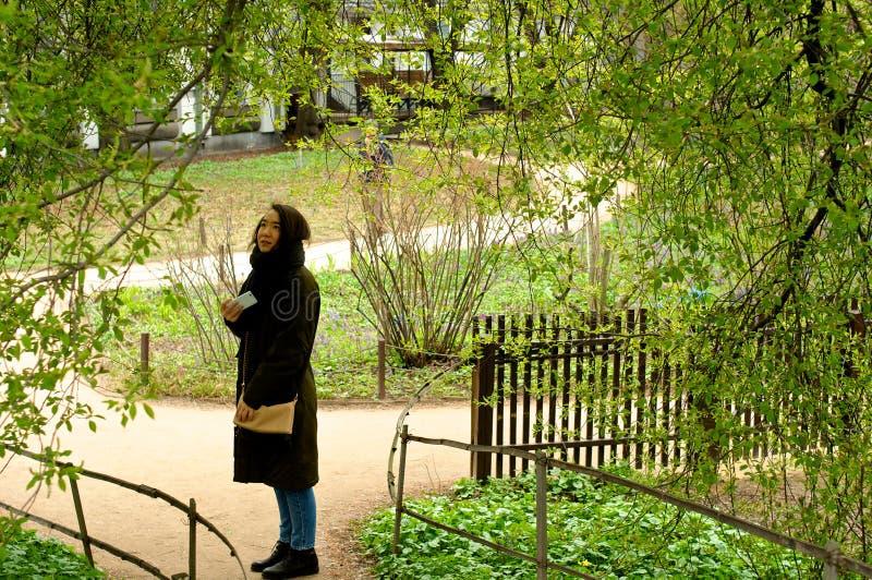 Menina ereta com o telefone no parque que olha acima imagem de stock