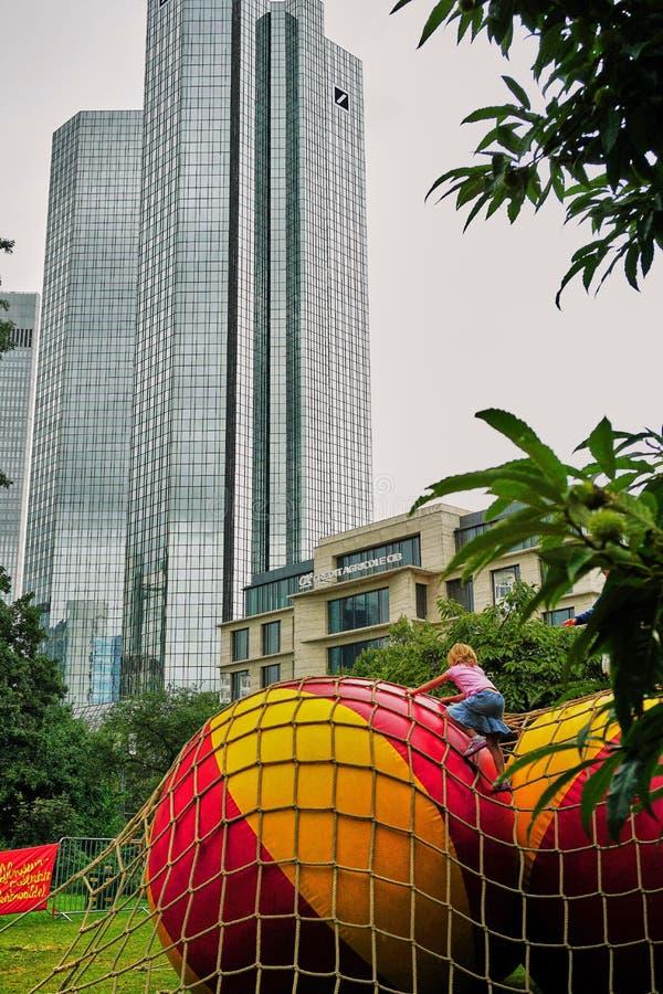 A menina escala bolas de praia enormes na selva urbana de Francoforte do centro imagem de stock