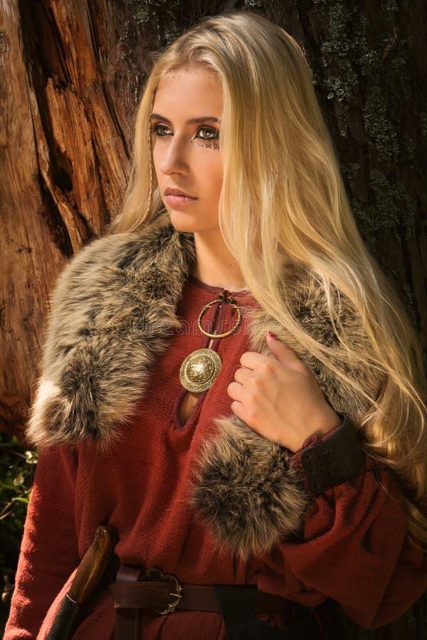 A menina escandinava com runic assina dentro uma madeira imagens de stock royalty free