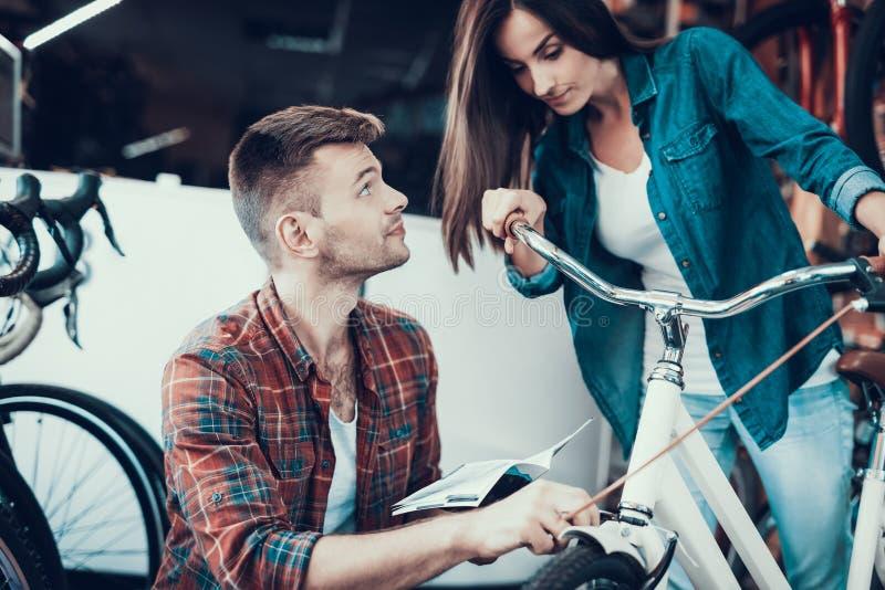 A menina escolhe a bicicleta da cidade com o amigo na loja do esporte imagem de stock royalty free