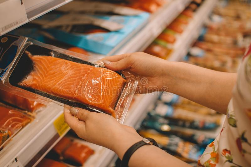 Menina escolhe comida enquanto faz compras no shopping do departamento de peixes Truta vermelha fresca na prateleira superior da fotografia de stock