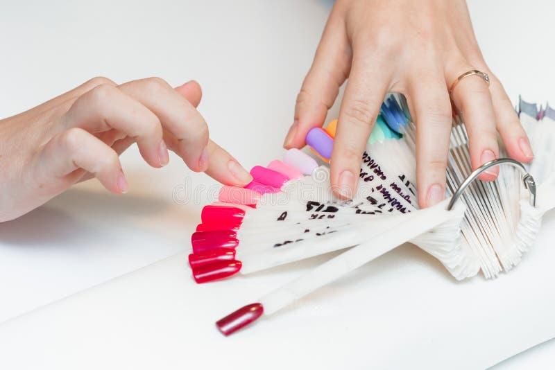 A menina escolhe a cor do polonês para o tratamento de mãos fotografia de stock royalty free