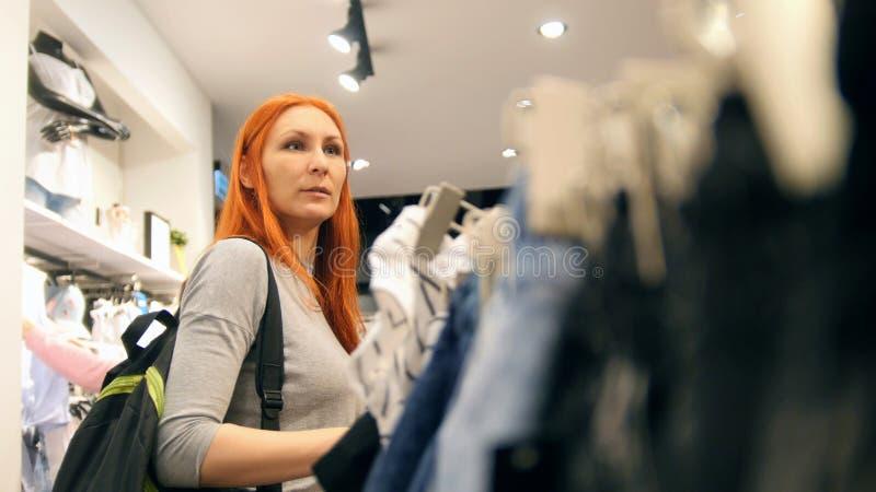 A menina escolhe o vestido na loja de roupa ou a alameda, mulher entre vestidos foto de stock royalty free