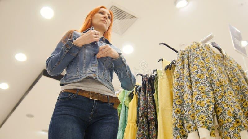 A menina escolhe um revestimento das calças de brim, comprando mulheres foto de stock royalty free