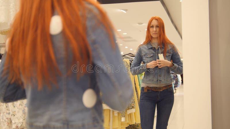 A menina escolhe um revestimento das calças de brim, comprando mulheres imagens de stock royalty free