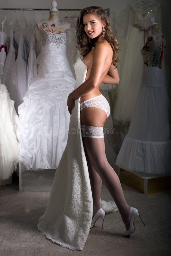 A menina escolhe um vestido de casamento fotos de stock