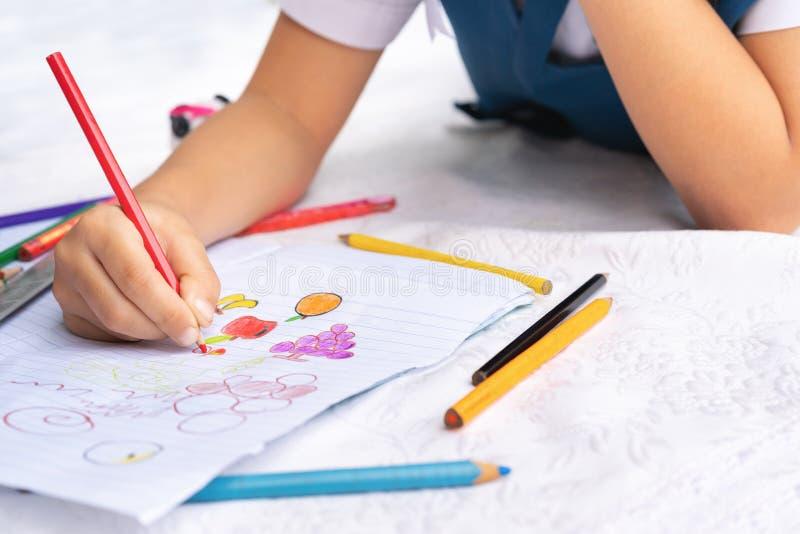 A menina escreve aos escrita-livros A decisão das lições a menina estabelece a tiragem da imagem foto de stock