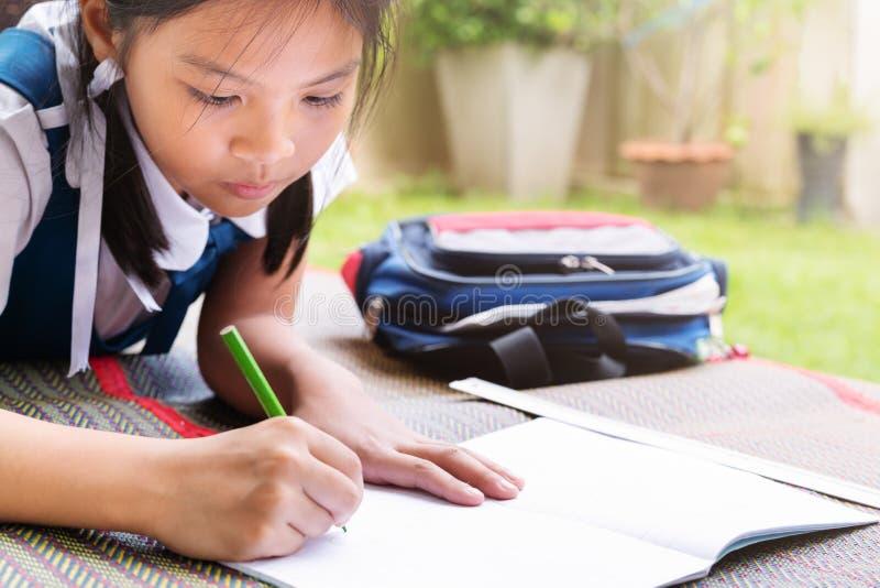 A menina escreve aos escrita-livros A decisão das lições a menina estabelece a tiragem da imagem imagens de stock