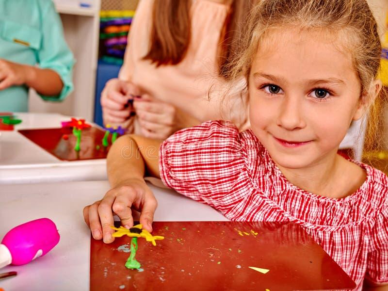 A menina esculpe do plasticine na mesa dentro imagens de stock