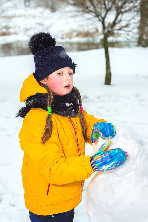 A menina esculpe o boneco de neve fotos de stock royalty free