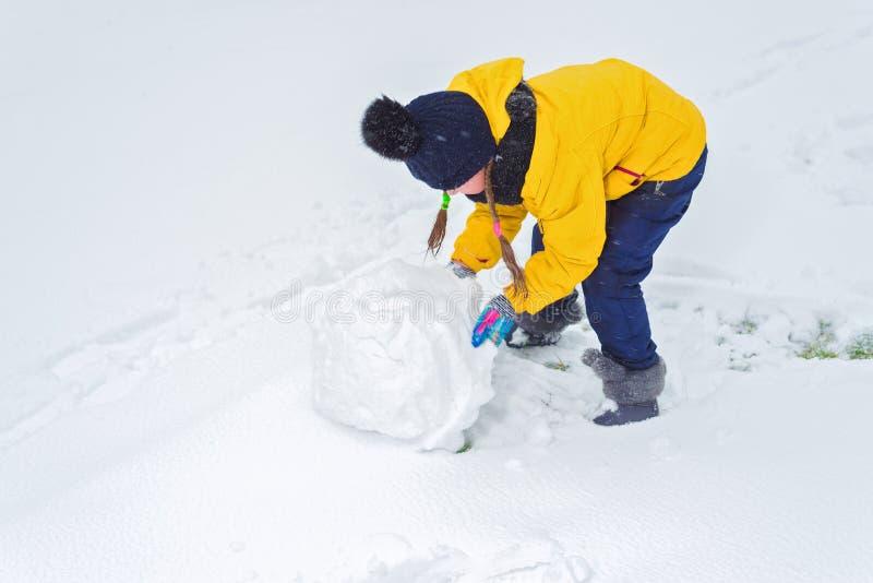 A menina esculpe o boneco de neve a criança está levando uma protuberância da neve imagem de stock
