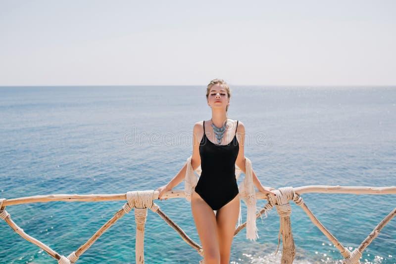 Menina escultural adorável no roupa de banho preto na moda que levanta contentemente com paisagem do oceano no fundo Mulher lindo imagens de stock royalty free