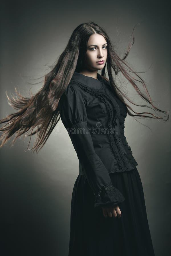 Menina escura bonita com cabelo longo do voo fotografia de stock royalty free