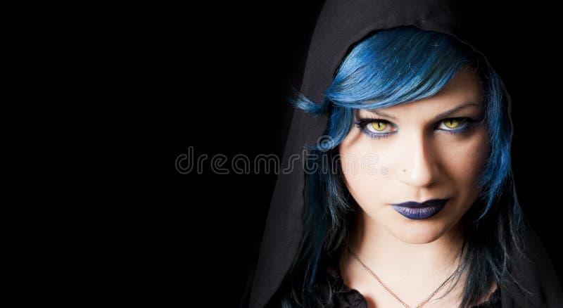 Menina escura com os olhos de gatos amarelos, cabelo azul e a capa preta foto de stock royalty free