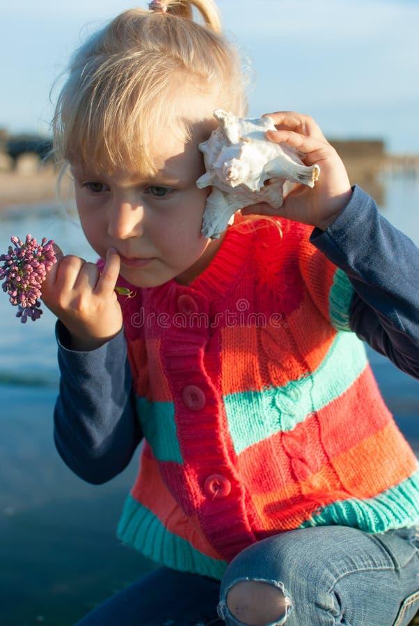 A menina escuta concha do mar foto de stock