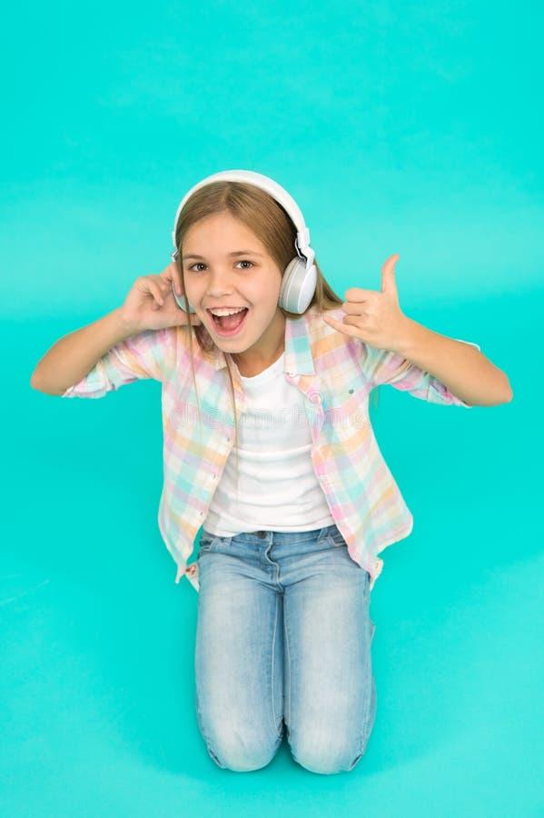 A menina escuta fones de ouvido da música Aprecie a trilha da faixa favorita A criança da menina escuta fones de ouvido modernos  fotos de stock royalty free