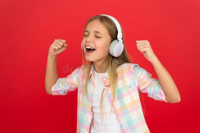 A menina escuta fones de ouvido da música Canal em linha da estação de rádio A criança da menina escuta fones de ouvido modernos  fotos de stock