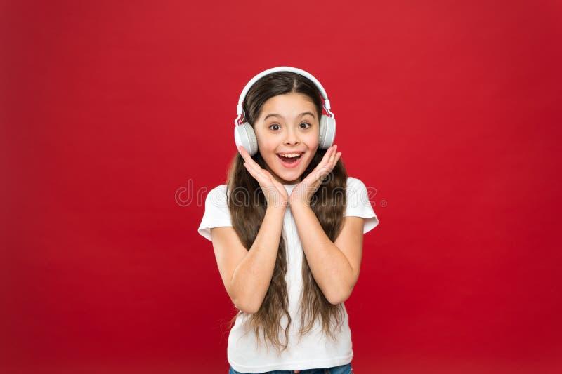 A menina escuta fones de ouvido da música no fundo vermelho Conceito da lista do jogo gosto da música A música joga vidas de uma  foto de stock royalty free