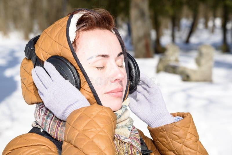 A menina escuta a música no inverno 2018 imagem de stock