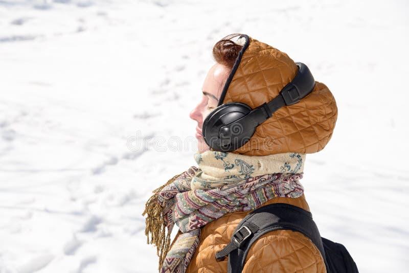 A menina escuta a música no inverno 2018 imagens de stock