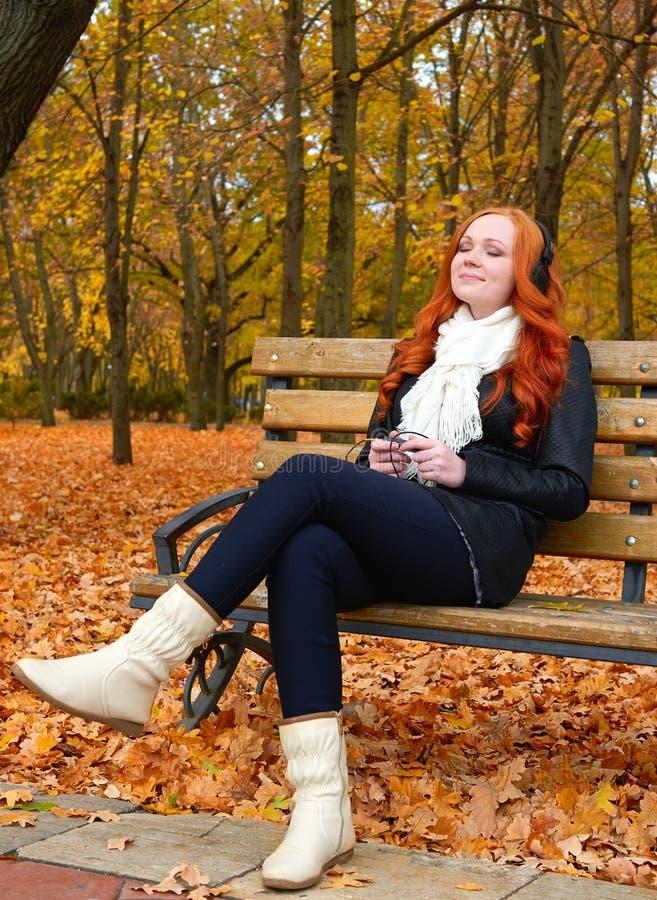 A menina escuta música no jogador audio com fones de ouvido, senta-se no banco no parque da cidade do outono, em árvores amarelas imagens de stock