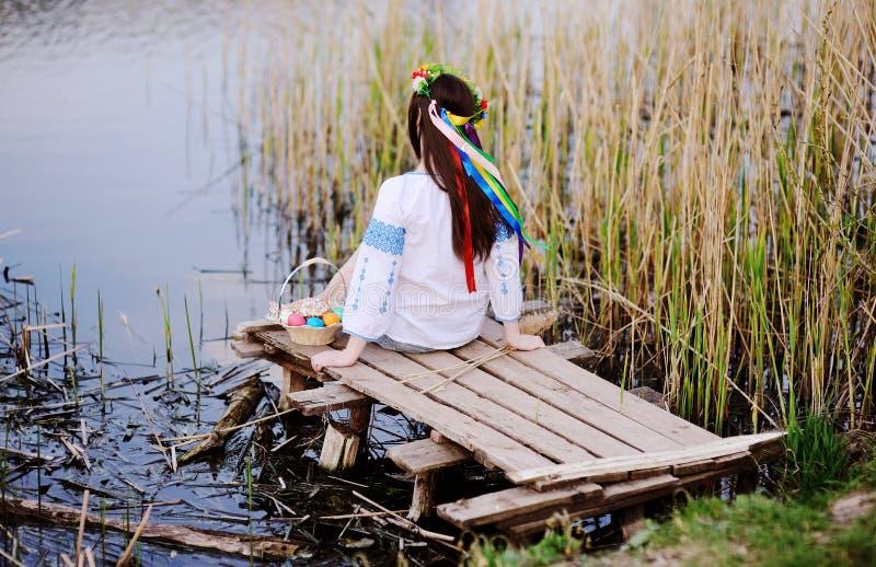 Menina eslavo na camisa ucraniana que senta-se na ponte com Páscoa foto de stock royalty free