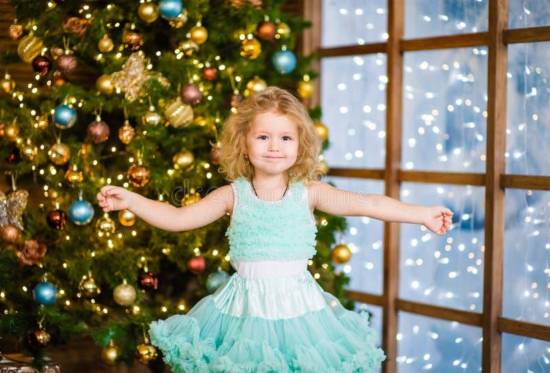 A menina espalhou seus braços ao lado perto da árvore de Natal imagens de stock royalty free