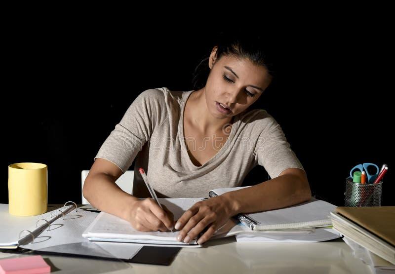 Menina espanhola bonita ocupada nova que estuda em casa a escrita de preparação de vista tardio do exame no bloco de notas fotografia de stock