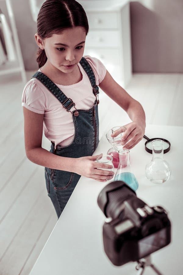 Menina esperta agradável que explica o que está fazendo imagem de stock