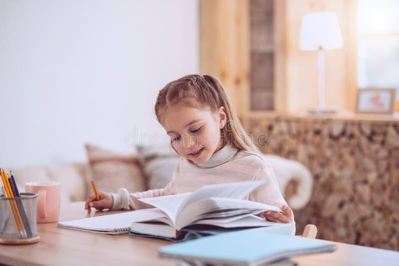 Menina esperta agradável que lê um livro imagem de stock