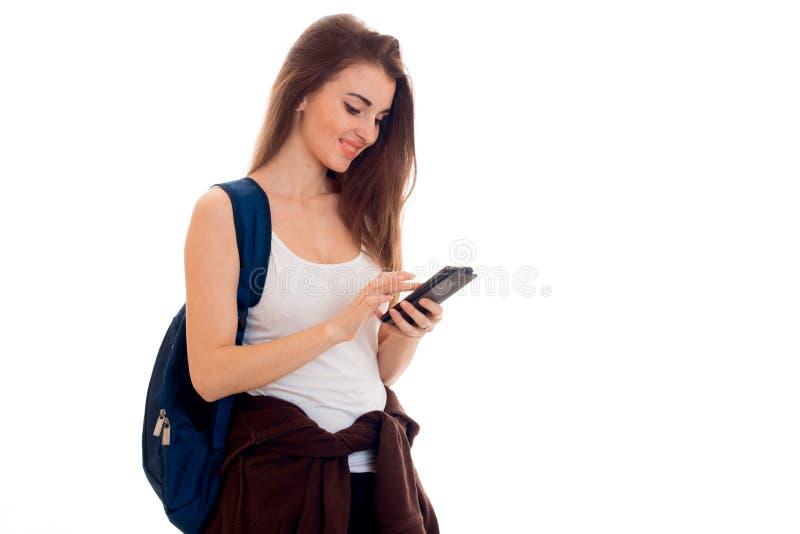 A menina esperta alegre do estudante no esporte marrom veste-se com a trouxa em seus ombros que olham seu telefone celular e foto de stock royalty free