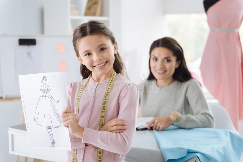 Menina esperta alegre que mostra seu esboço do projeto imagens de stock royalty free