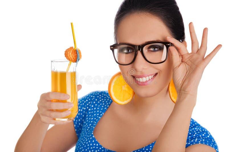 Menina esperta com suco de laranja e fundo alaranjado do branco dos brincos da fatia fotografia de stock royalty free