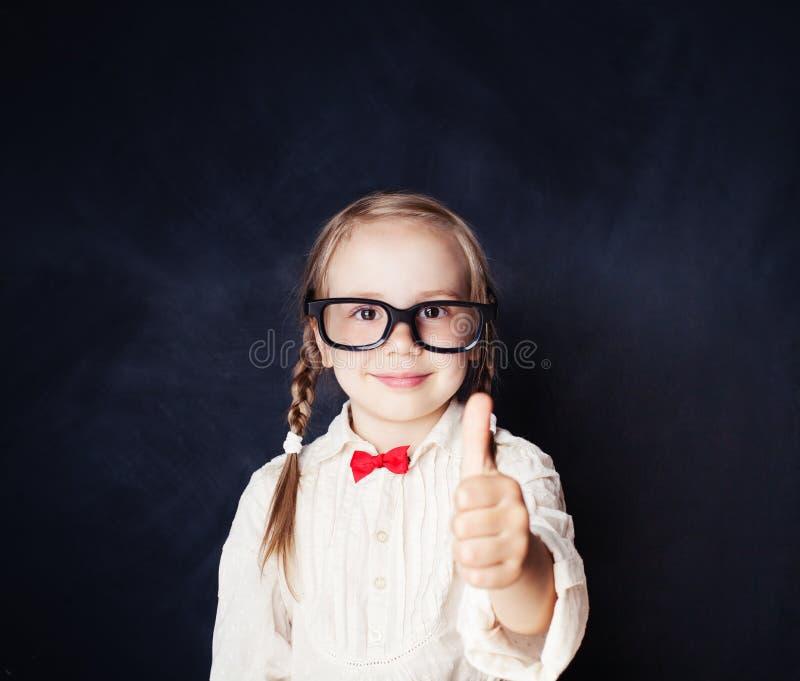Menina esperta nos vidros com o polegar acima que tem o divertimento na placa de giz fotos de stock royalty free