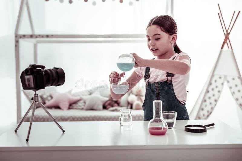 Menina esperta positiva que toma um vídeo para seu blogue da ciência imagem de stock royalty free