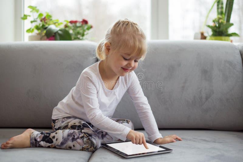 Menina esperta que usa o tablet pc ao sentar-se no sofá na sala de visitas em casa fotos de stock royalty free