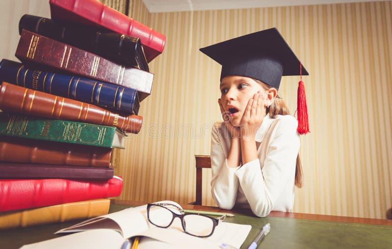 Menina esperta surpreendida no tampão da graduação que olha o montão grande dos livros imagem de stock royalty free