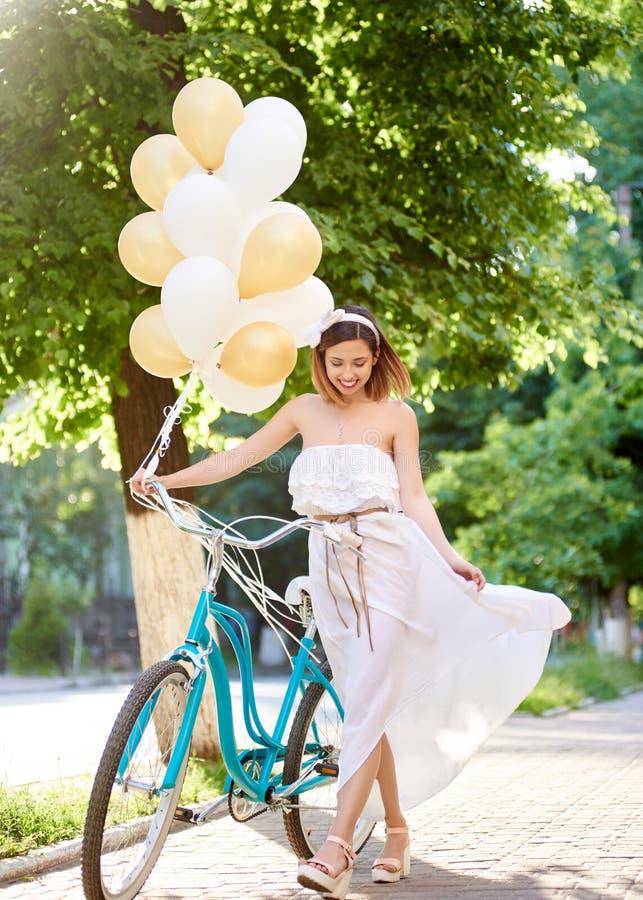 A menina está andando ao longo da rua da cidade com bicicleta e balões fotos de stock