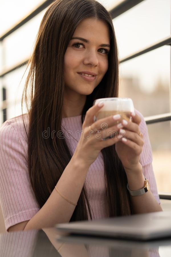 A menina está apreciando o café Uma xícara de café nas mãos fêmeas Na tabela ? um port?til fechado imagens de stock royalty free