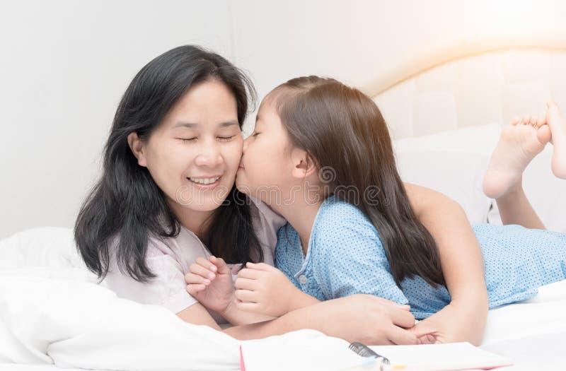 A menina está beijando sua mamã nova bonita no mordente fotografia de stock