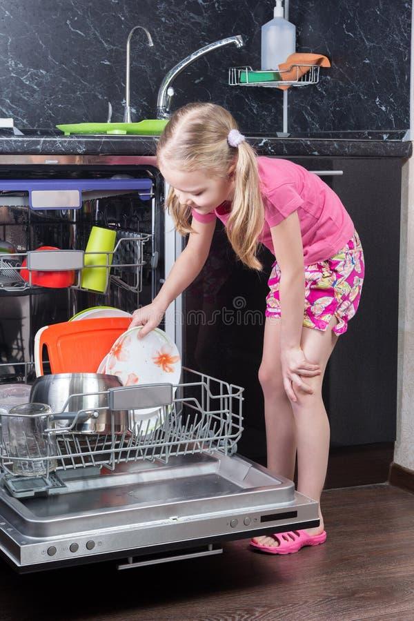 A menina está carregando pratos na máquina de lavar louça fotos de stock royalty free
